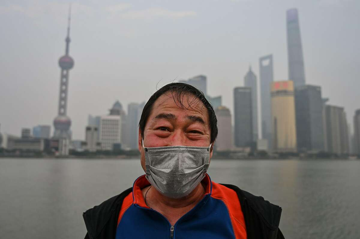 TOPSHOT - A man wears a protective face mask on the promenade of the Bund along the Huangpu River in Shanghai on February 25, 2020. - The new coronavirus has peaked in China but could still grow into a pandemic, the World Health Organization warned, as infections mushroom in other countries. (Photo by Hector RETAMAL / AFP) (Photo by HECTOR RETAMAL/AFP via Getty Images)