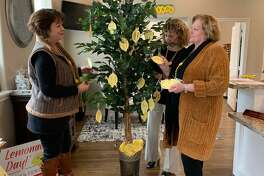 Friendswood Chamber of Commerce membership coordinator Joanne Edge, left, joins chamber vice president Dianne Hass and president Carol Marcantel in looking at paper lemons with names of donors for the community's first Lemonade Day, set for May 2 .