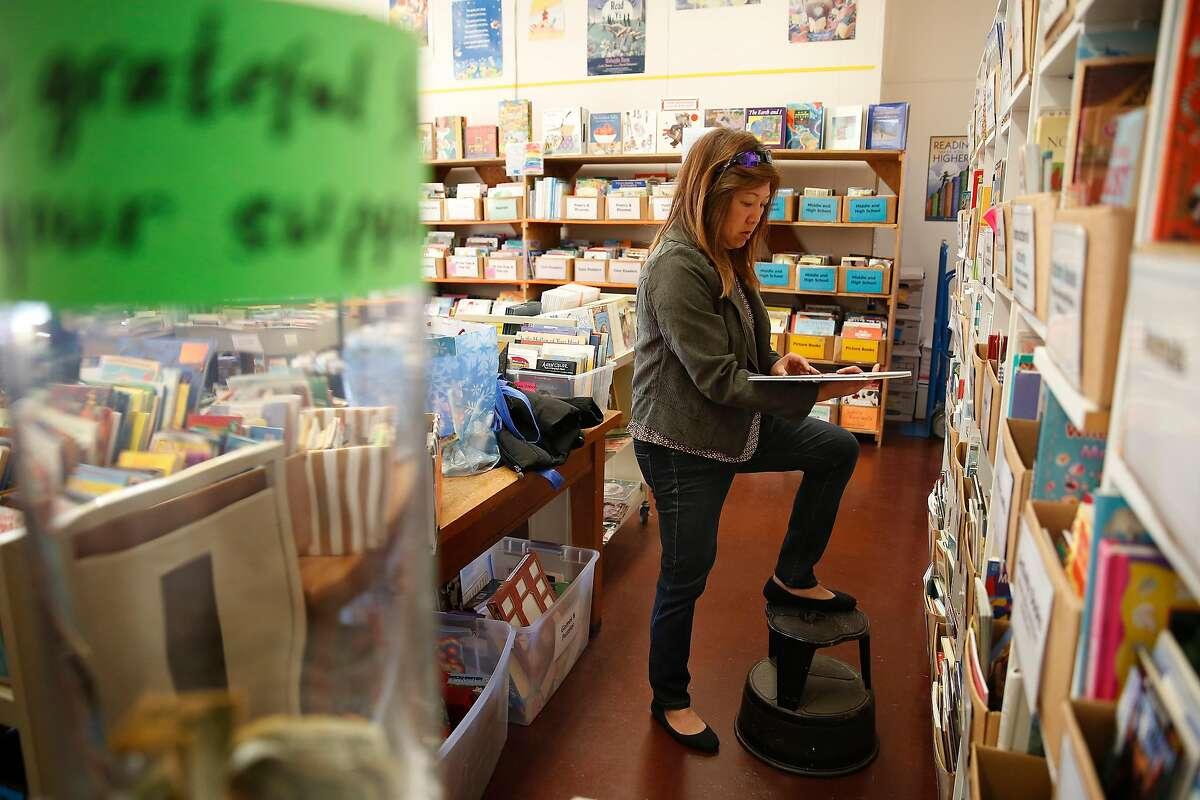 Michelle Low, Robert Louis Stevenson Elementary School teacher, looks over books on shelves at the Children's Book Project on Monday, February 24, 2020 in San Francisco, Calif.