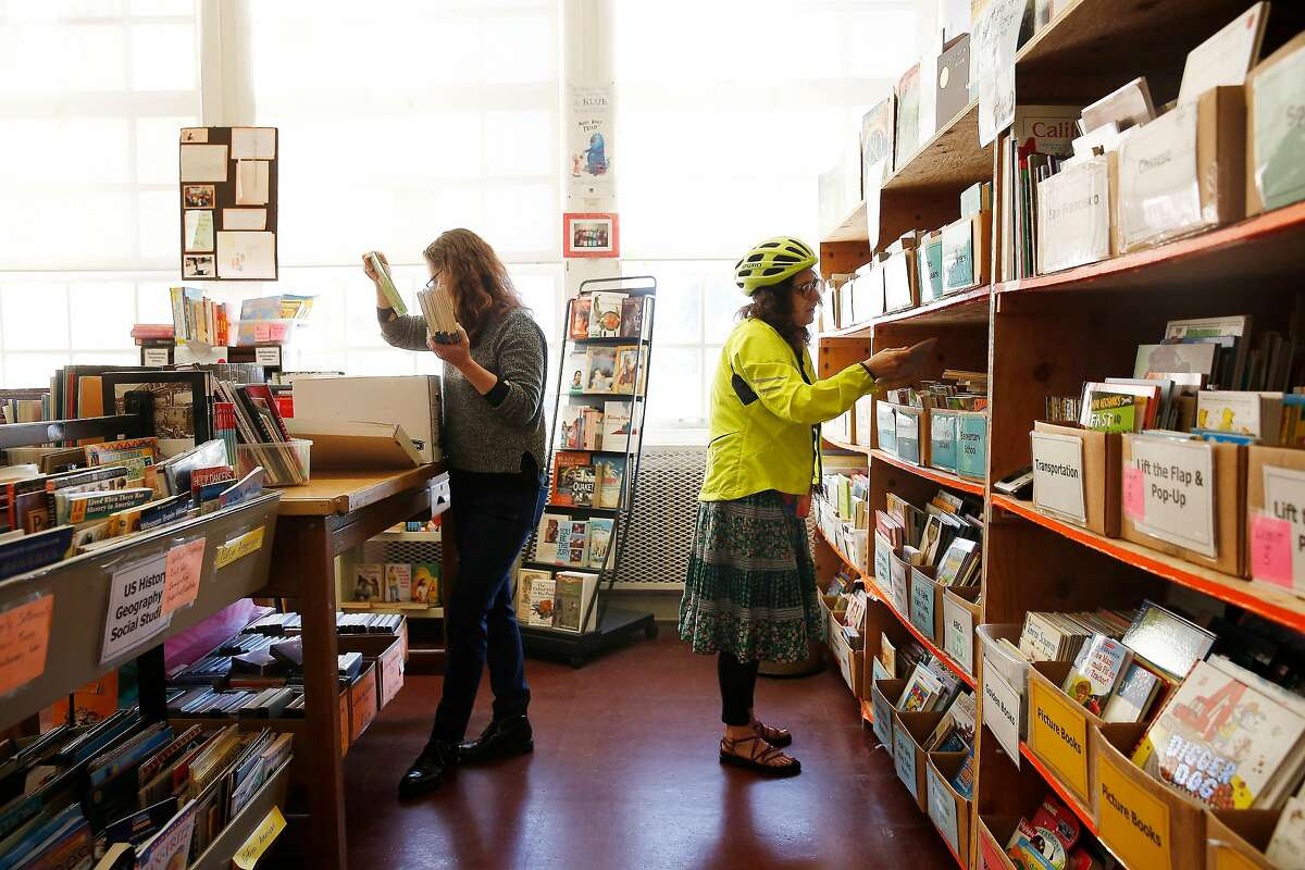 Kathleen Wydler (l to r), book site manager, takes books from a box to shelve them, as Ellen Kerr , George Washington High School english second language teacher, looks for books for students at the Children's Book Project on Monday, February 24, 2020 in San Francisco, Calif.