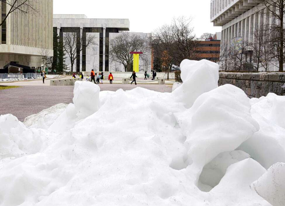 A remnant of snow from a larger pile still remains in a corner of the Empire State Plaza as people get out to enjoy the warm weather on Tuesday, Feb. 25, 2020, in Albany, N.Y. (Paul Buckowski/Times Union)
