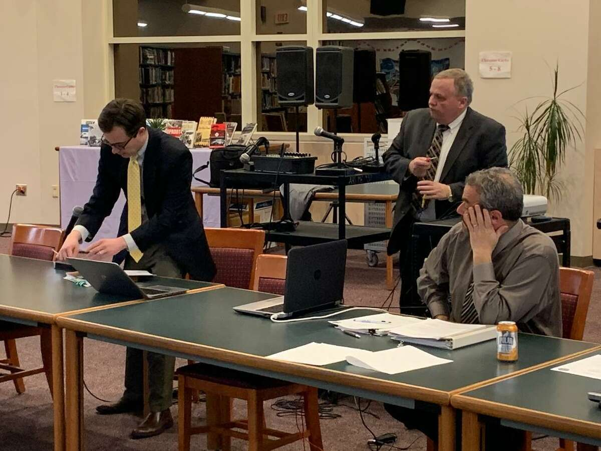 Matt Venhorst, a lawyer with the state Department of Education, adjusts his laptop while discussing the curriculum and course study requirements for a regionalized school district with members of the Ansonia-Derby Temporary School Regionalization Study Committee during the Feb. 24, 2020 meeting. Standing behind him is George Kurtyka while Jim Gildea is seated. Both are committee members.