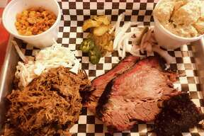 A plate of brisket and pulled pork with sides of smoked corn and potato salad at The Hot Box.