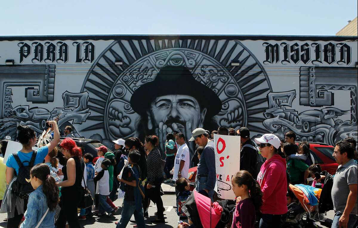 A group of people walk past a mural near the corner of 19th and Mission Streets during the Cesar Chavez Day Parade in the Mission District of San Francisco, Calif. Saturday, April 18, 2015