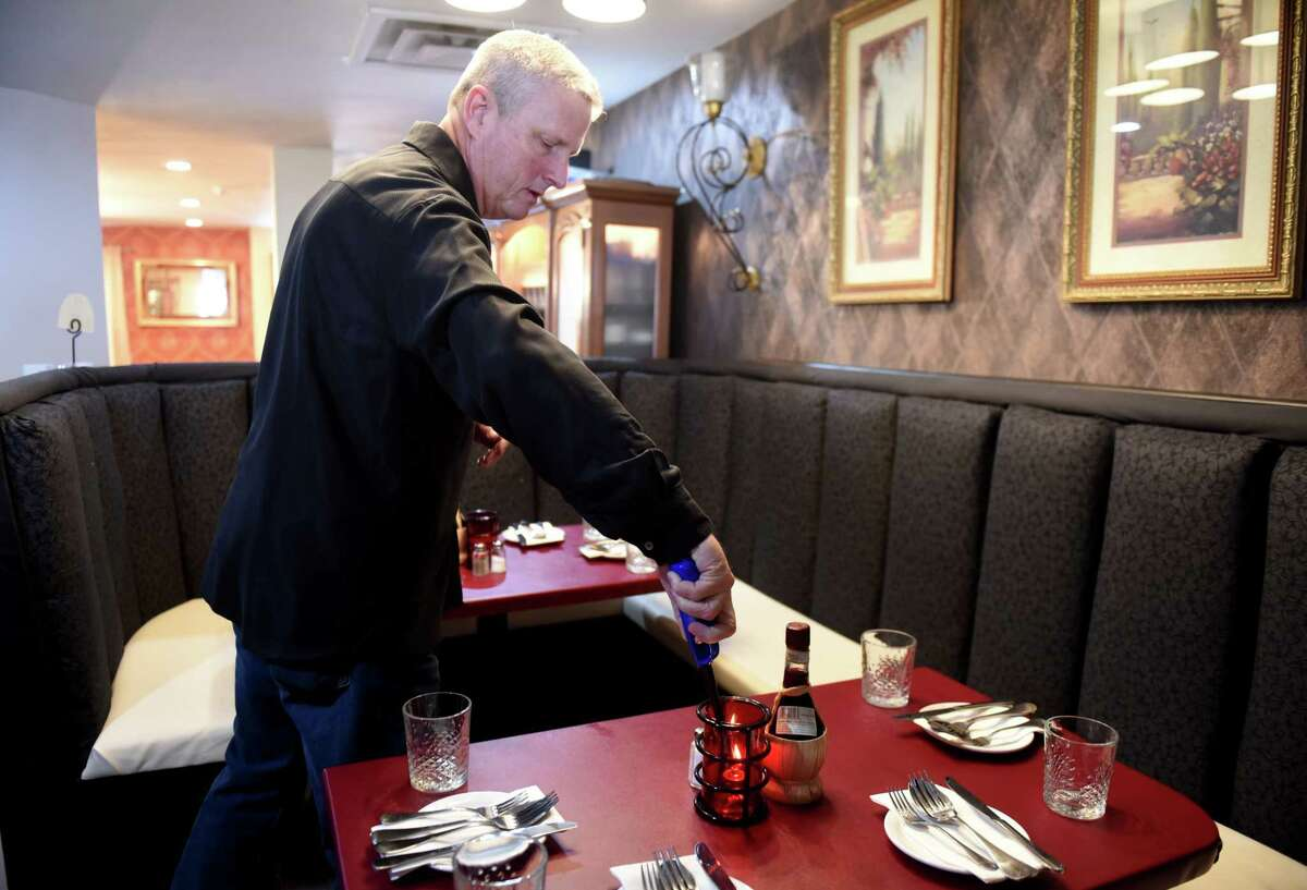 Bob Barbieri, one the three co-owners of Anthony's Restaurant, lights table candles during a ribbon cutting event on Tuesday, Feb. 25, 2020, in Cohoes, N.Y. The building was part of the 2017 Remsen Street fire, and was slated for demolition. (Will Waldron/Times Union)