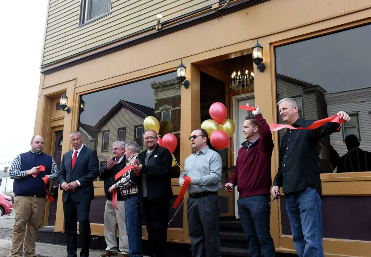 Anthony's Restaurant co-owners; Bob Barbieri, right, Derek Villaneuve, second from right, and Don Russell, celebrate during a ribbon cutting event to mark their restaurant's opening on Tuesday, Feb. 25, 2020, in Cohoes, N.Y. The building was part of the 2017 Remsen Street fire, and was slated for demolition. (Will Waldron/Times Union)