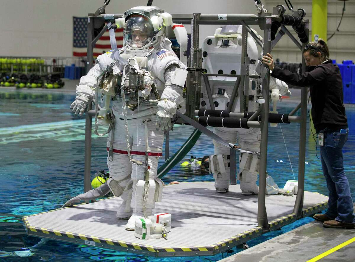 Astronauts Anne McClain, left, and Zena Cardman are being lowered into NASA's Neutral Buoyancy Laboratory for spacewalk training on Tuesday, Feb. 25, 2020, in Houston.