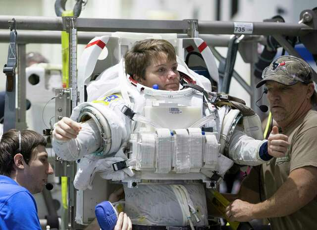 Suit Engineer Wesley Wilson, left, and Suit Technician Don Smith help astronaut Anne McClain to suit up for spacewalk training at NASA's Neutral Buoyancy Laboratory on Tuesday, Feb. 25, 2020, in Houston.