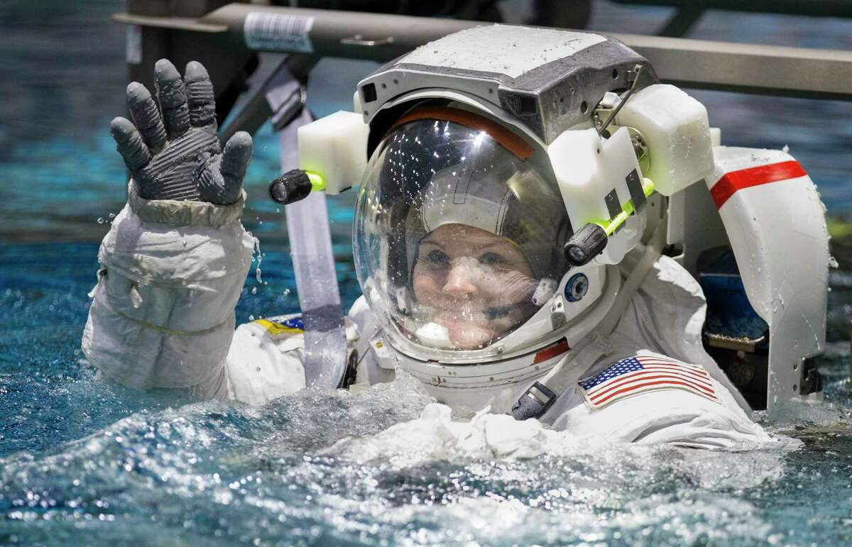 Astronaut Anne McClain waves at the audience while being lowered into the Neutral Buoyancy Lab for space walk training next to the International Space Station mockup Tuesday, Feb. 25, 2020, at Johnson Space Center in Houston.
