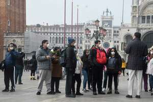 Tourists wearing protective masks visit Venice on Feb. 25, 2020, during the usual period of the Carnival festivities which have been cancelled following an outbreak of the COVID-19 novel coronavirus in northern Italy.