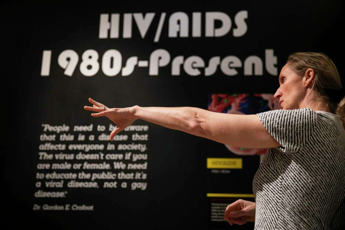 Becky Seabrook, Health Museum senior director of engagement, gives a tour of the Outbreak exhibit on Tuesday, Feb. 18, 2020. A section of the exhibit focuses on the HIV outbreak in Houston featuring local memorabilia and information from Houstonians.