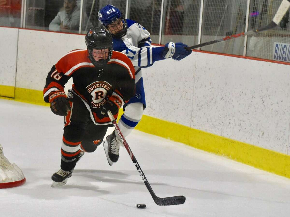 Ridgefield defenseman Kevin McNicholas (16) gets out in front of Darien's Jamison Moore on Friday.