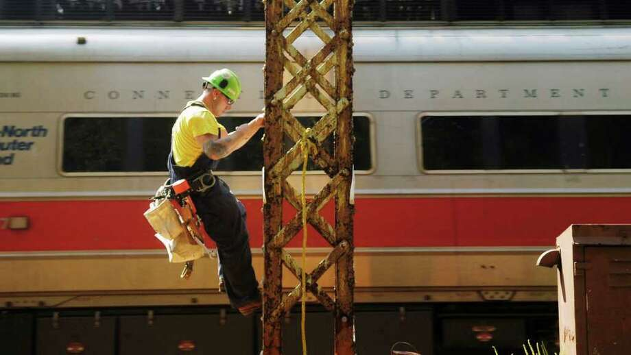 FILE: A Metro-North Railroad electrical line man, climbs down a tower after grounding a power line to create a safe area for working on the overhead wires. Photo: File Photo / Stamford Advocate File Photo