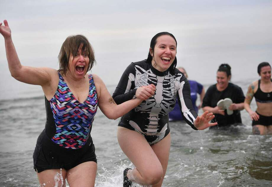 University of Bridgeport School of Naturopathic Medicine Professor Cynthia Anderson, left, and third year student Brenda Bithoney exit the Sound hand in hand during the school's fifth annual polar plunge at Seaside Park in Bridgeport, Conn. on Tuesday, February 25, 2020. Photo: Brian A. Pounds / Hearst Connecticut Media / Connecticut Post