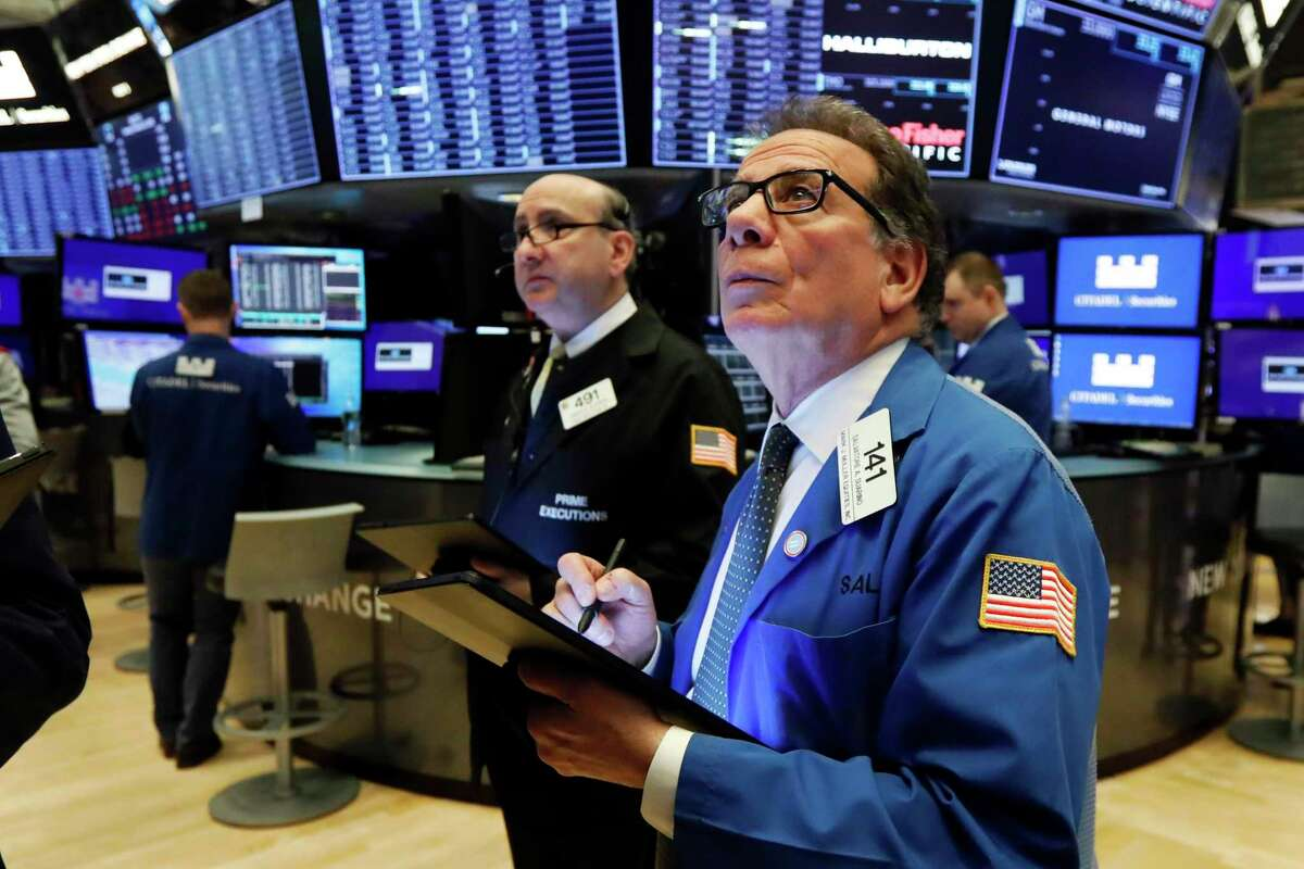 Traders Andrew Silverman (left) and Sal Suarino, on the floor of the New York Stock Exchange, watch monitors displaying the changing prices.