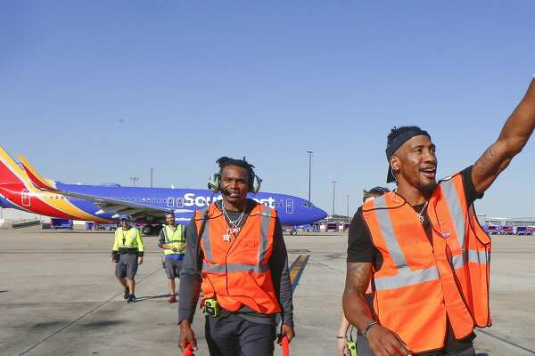 Houston Rockets Robert Covington (r) and Danuel House walk back to the terminal after aiding with ta Southwest Airlines departure at William H. Hobby Airport Tuesday, Feb. 25, 2020, in Houston.