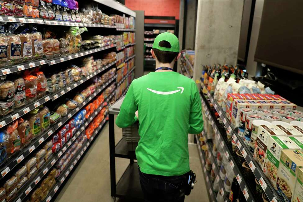 In this Feb. 21, 2020 photo, a worker pushes a cart inside an Amazon Go Grocery store set to open soon in Seattle's Capitol Hill neighborhood. Following the opening of several smaller convenience-type stores using an app and cashier-less technology to tally shoppers' selections, the store will be the first Amazon Go full-sized cashier-less grocery store. (AP Photo/Ted S. Warren)