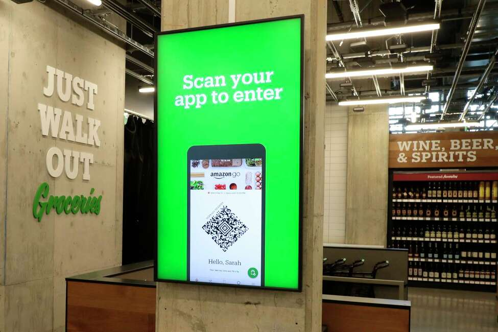 In this Feb. 21, 2020 photo, a sign tells shoppers how to check in when they enter an Amazon Go Grocery store set to open soon in Seattle's Capitol Hill neighborhood. Following the opening of several smaller convenience-type stores using an app and cashier-less technology to tally shoppers' selections, the store will be the first Amazon Go full-sized cashier-less grocery store. (AP Photo/Ted S. Warren)