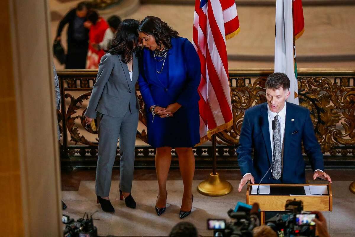 (L-r) Assessor Carmen Chu chats with Mayor London Breed during a press conference to announce a state of emergency due to the global outbreak of the coronavirus at City Hall on Tuesday, Feb. 25, 2020 in San Francisco, California.The City has increased its preparedness for a potential outbreak.