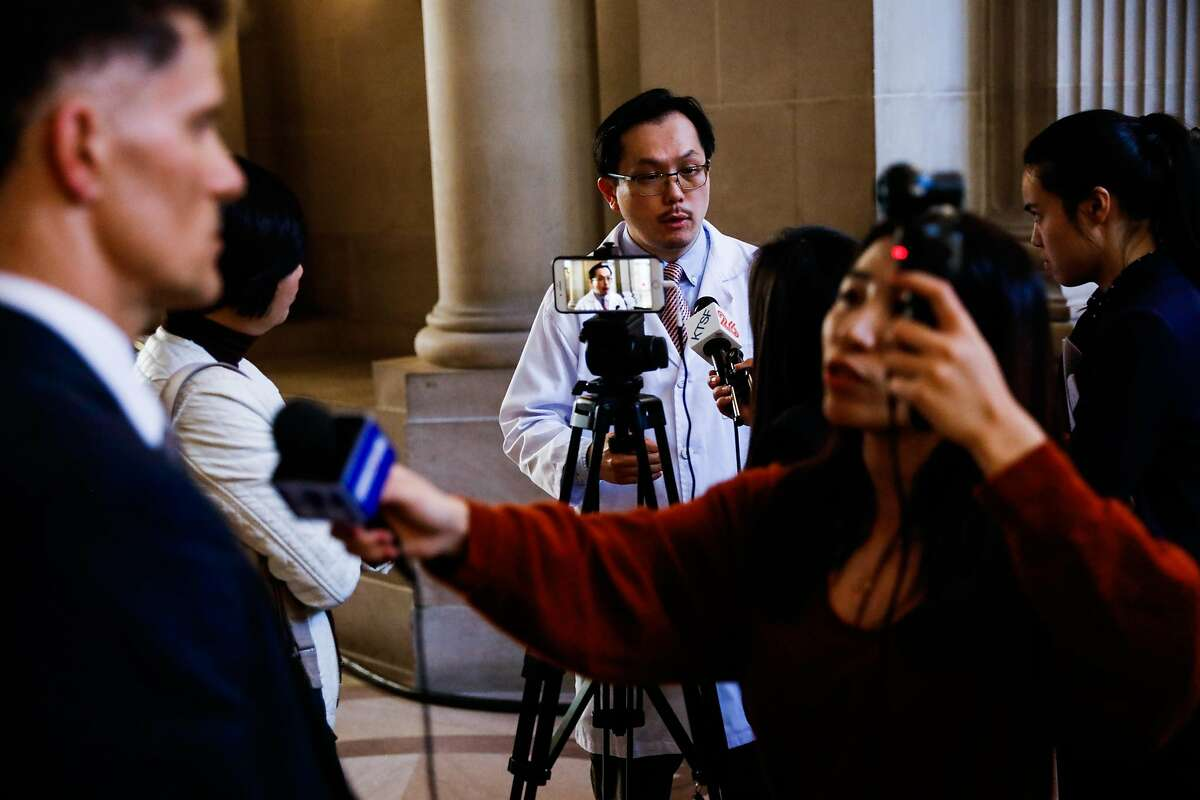 Dr. Sunny Pak (center) speaks with the media following a press conference to announce a state of emergency due to the global outbreak of the coronavirus at City Hall on Tuesday, Feb. 25, 2020 in San Francisco, California.The City has increased its preparedness for a potential outbreak.