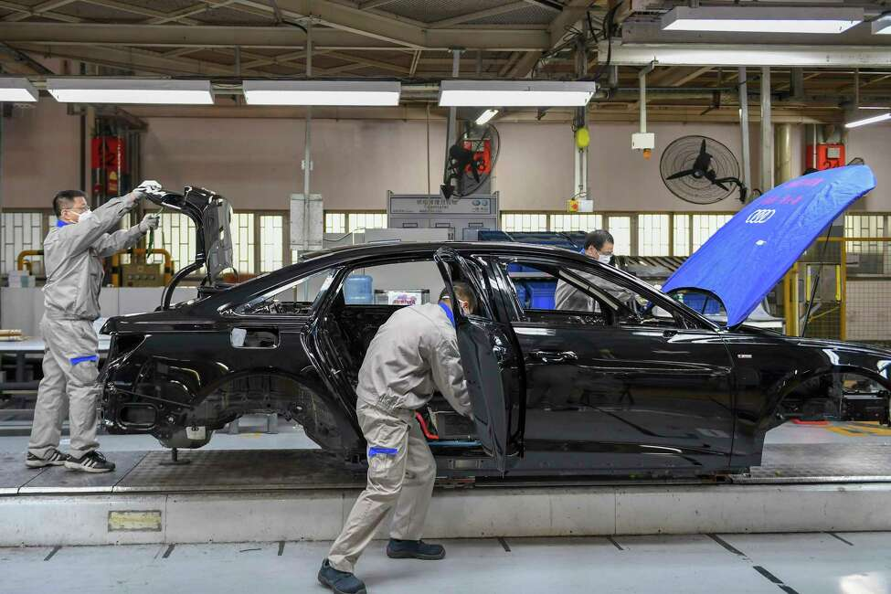 In this Feb. 17, 2020, file photo released by Xinhua News Agency, workers assemble Audi A6 L cars at a workshop of FAW-Volkswagen Automobile Co., Ltd. in Changchun, northeast China's Jilin Province.Factories that make the world's smartphones, toys and other goods are struggling to reopen after a virus outbreak idled China's economy. But even with the ruling Communist Party promising help, companies and economists say it may be months before production is back to normal. (Zhang Nan/Xinhua via AP, File)