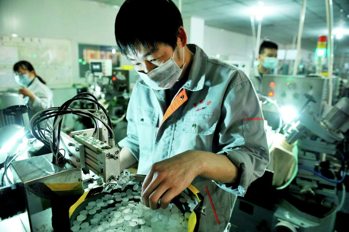 In this photo taken Feb. 23, 2020, workers make optical lenses in a factory in Dexing city in central China's Jiangxi province. Factories that make the world's smartphones, toys and other goods are struggling to reopen after a virus outbreak idled China's economy. But even with the ruling Communist Party promising help, companies and economists say it may be months before production is back to normal. (Chinatopix Via AP)