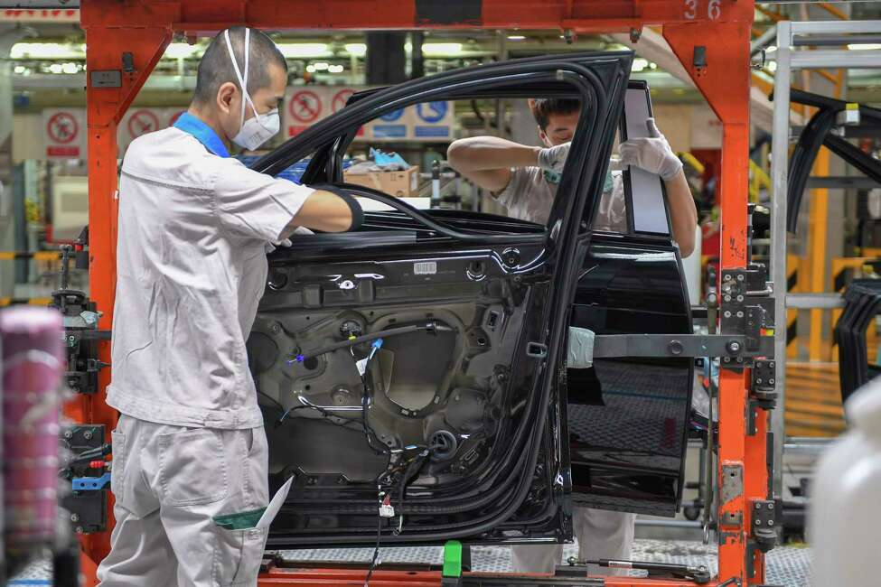In this Feb. 17, 2020, file photo released by Xinhua News Agency, workers assemble Audi A6 L cars at a workshop of FAW-Volkswagen Automobile Co., Ltd. in Changchun, northeast China's Jilin Province. Factories that make the world's smartphones, toys and other goods are struggling to reopen after a virus outbreak idled China's economy. But even with the ruling Communist Party promising help, companies and economists say it may be months before production is back to normal. (Zhang Nan/Xinhua via AP, File)