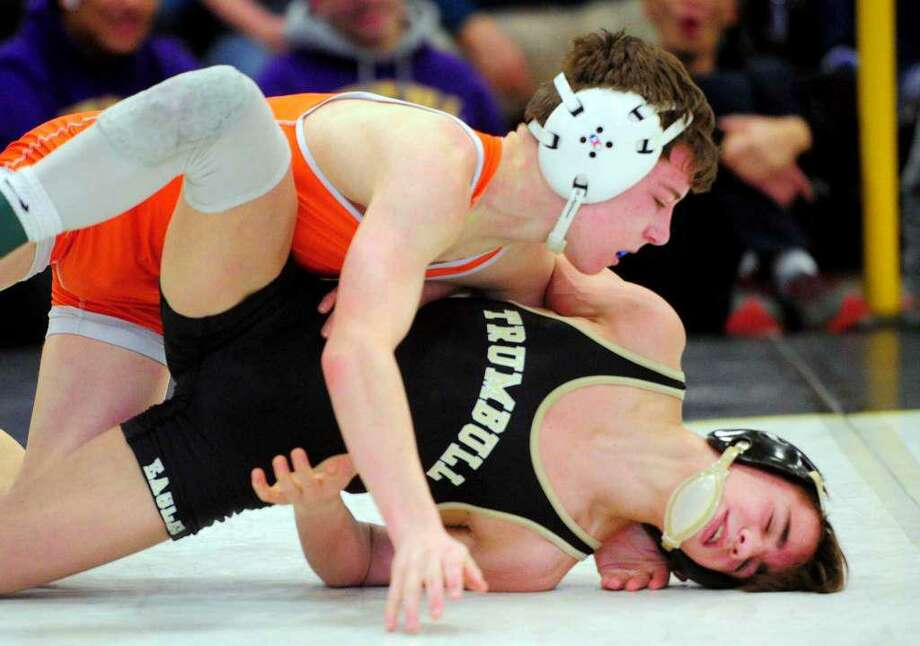Ridgefield's Alex Blaha (left) battles Trumbull's Michael Longo in the 106-pound finals at the Class LL wrestling championships. Photo: Christian Abraham / Hearst Connecticut Media