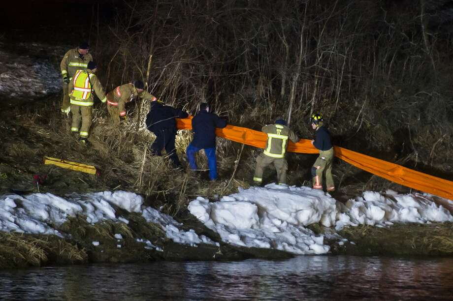 Firefighters from multiple local fire departments work to contain a spill on Pine River near S. Woodcock Road Tuesday, Feb. 25, 2020 in Midland. The Michigan Department of Environment, Great Lakes, and Energy determined the substance to be dielectric fluid that leaked from a transformer. A St. Louis area resident had obtained the transformer in the hopes of scrapping the metal and while transferring the liquid inside to three 55-gallon drums, it leaked out and made its way to the river. (Katy Kildee/kkildee@mdn.net) Photo: (Katy Kildee/kkildee@mdn.net)