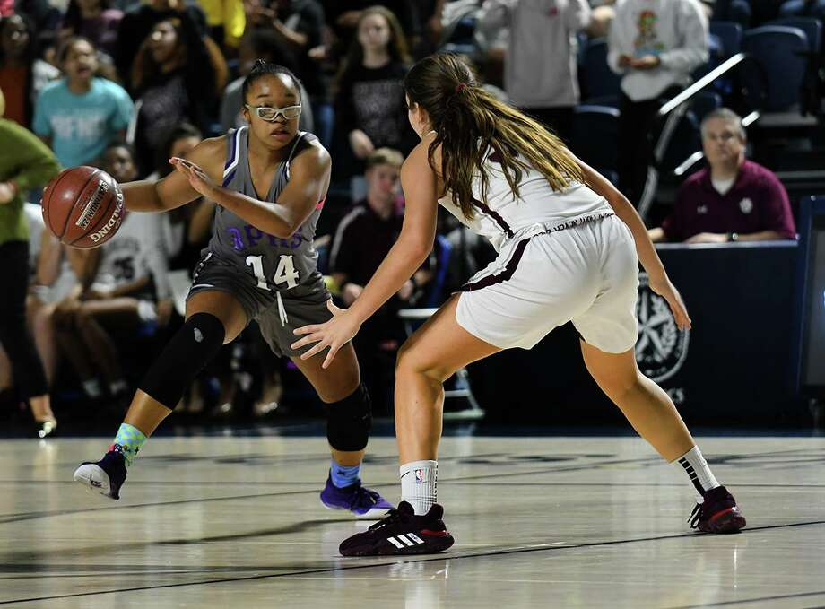 Ridge Point junior guard Aleighyah Fontenot, left, dribbles as Cy-Fair sophomore Olaia Arenas defends during the fourth quarter of a Region III-6A quarterfinal at Delmar Fieldhouse. Fontenot tied her school record with nine 3-pointers for a game-high 28 points. Photo: Jerry Baker, Houston Chronicle / Contributor / Houston Chronicle