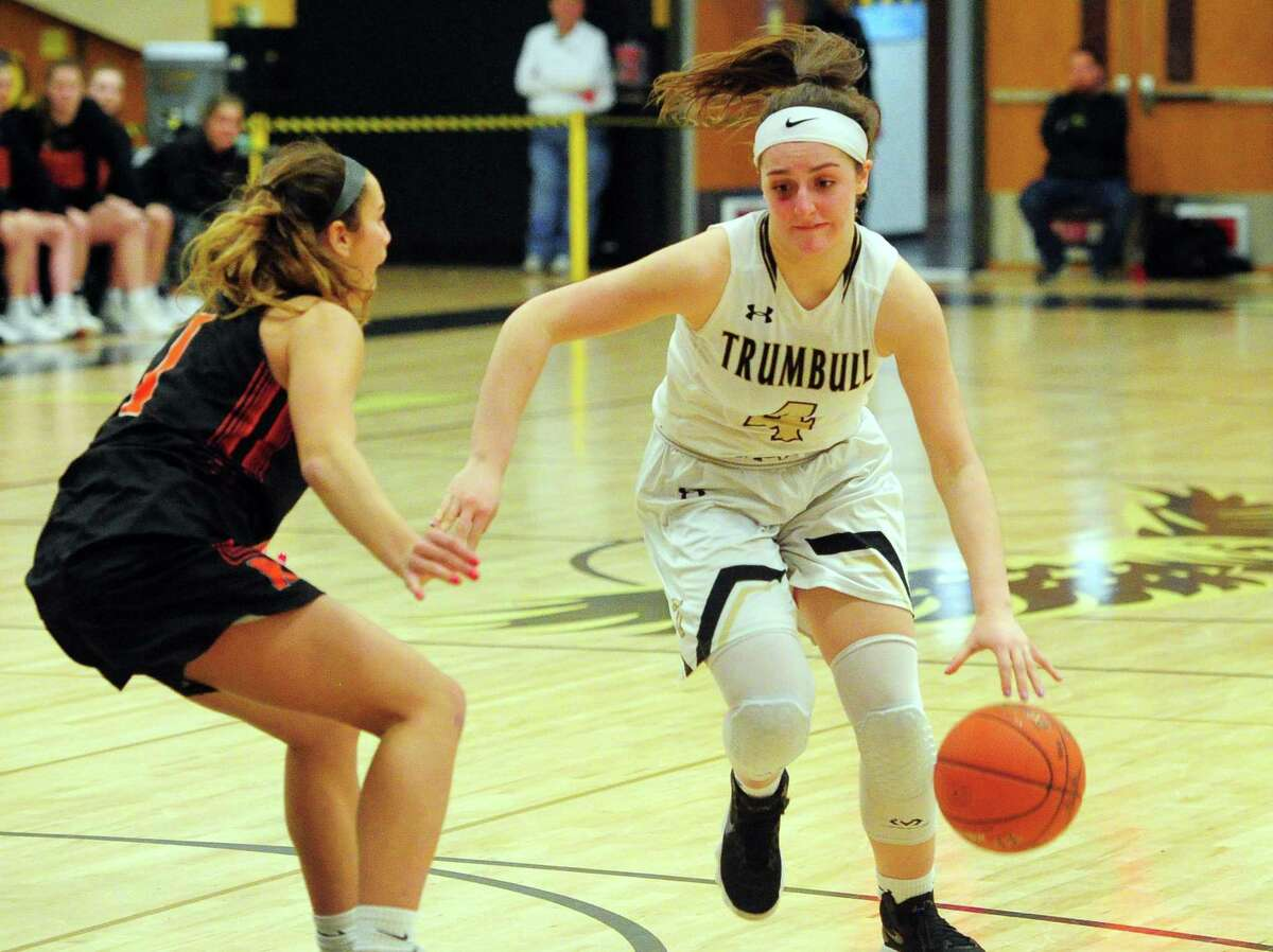 Trumbull's Sarah Stolze (4) drives to the basket as Ridgefield's Maya Rubio defends during FCIAC Girls' Basketball Quarterfinals action in Trumbull, Conn., on Tuesday Feb. 25, 2020.