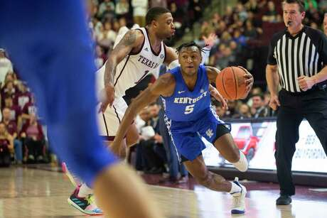 A&M's Savion Flagg, left, attempts a steal against Kentucky's Immanuel Quickley, who erupted for a career-high 30 points.