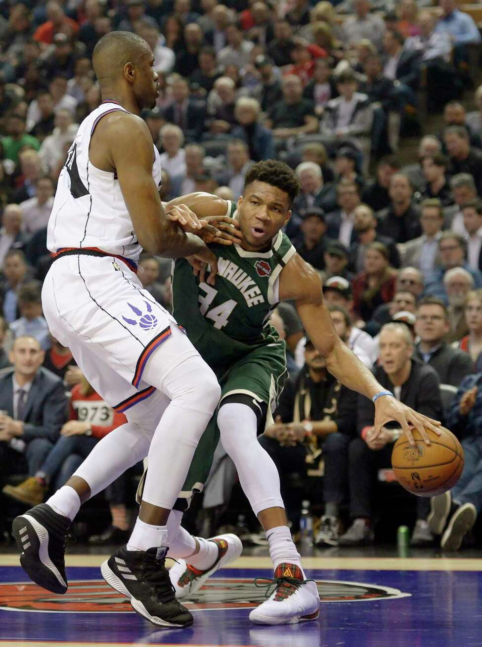 Milwaukee Bucks forward Giannis Antetokounmpo (34) tries to get around Toronto Raptors center Serge Ibaka during the first half of an NBA basketball game Tuesday, Feb. 25, 2020, in Toronto. (Nathan Denette/The Canadian Press via AP)