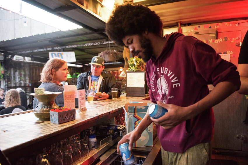 Eli's bartender Malik Mays stocks a cooler to the brim with cans of Montucky.