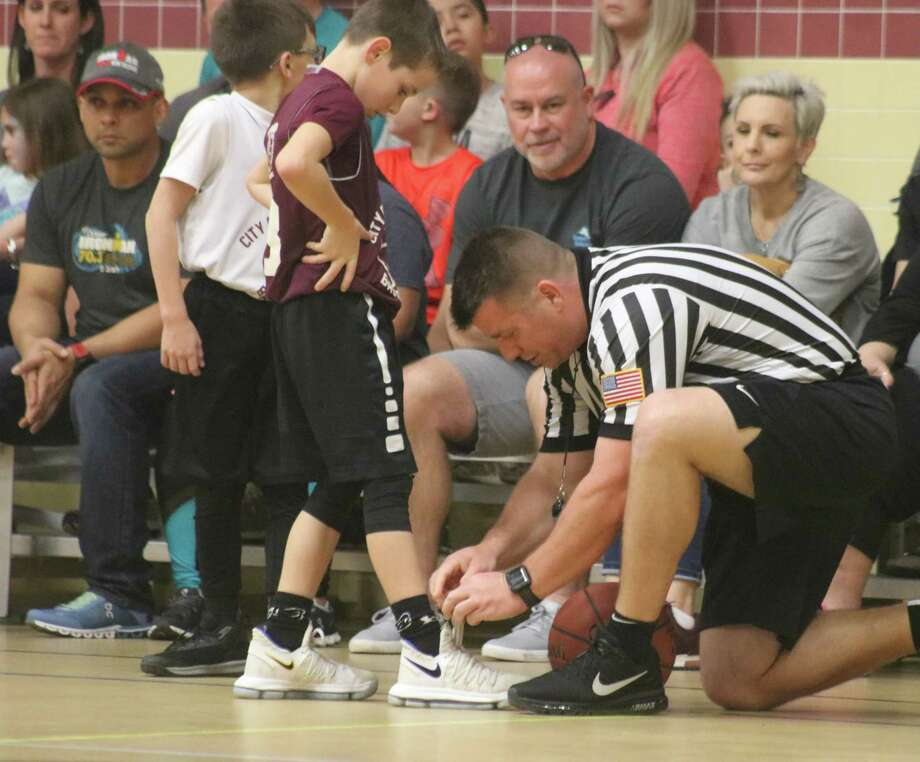 Referee Heath Harvey may or may not be tying shoelaces like he did for this youngster during a 2019 City Championship game, but he'll be one of the refs for this Saturday's excitement when city titles are handed out. Photo: Robert Avery
