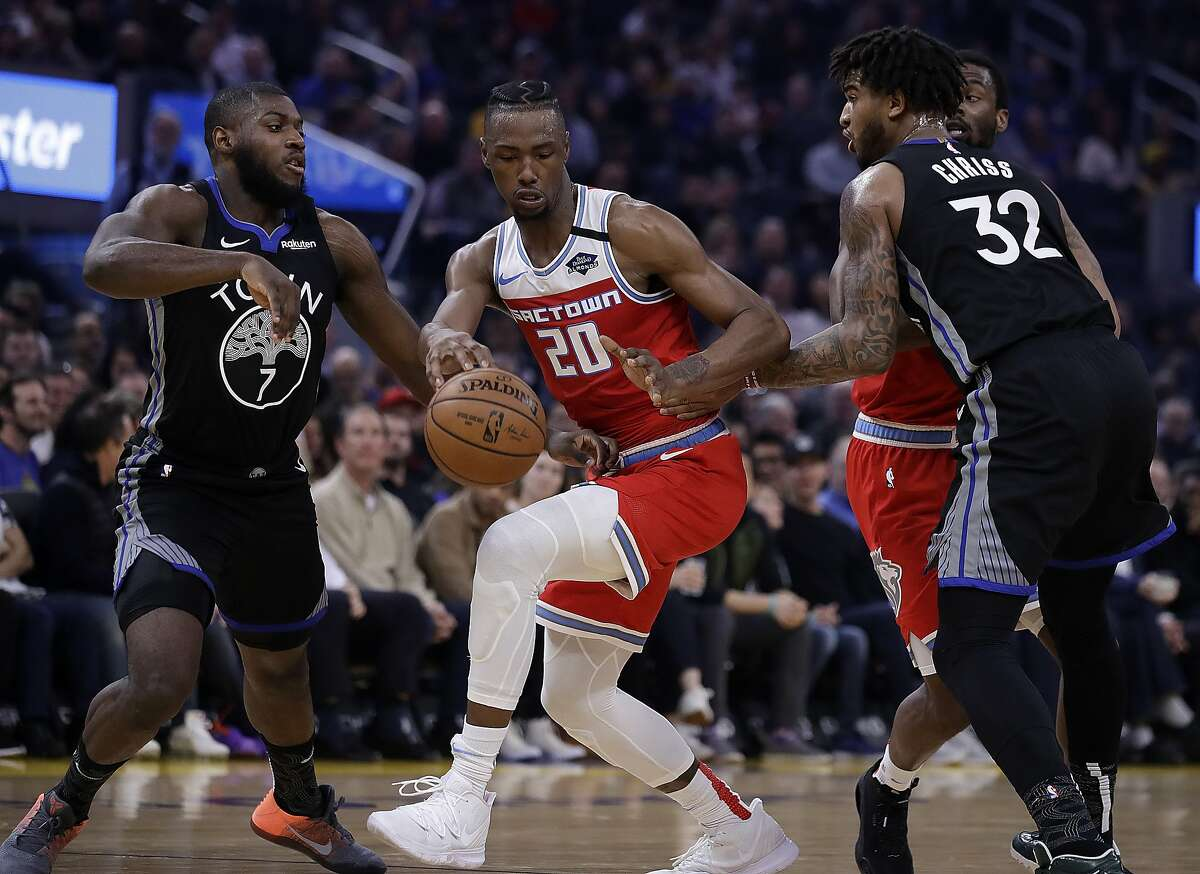 Sacramento Kings' Harry Giles III (20) drives the ball between Golden State Warriors' Eric Paschall, left, and Marquese Chriss (32) during the first half of an NBA basketball game Tuesday, Feb. 25, 2020, in San Francisco. (AP Photo/Ben Margot)