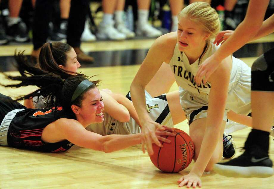 Ridgefield's Cara Sheafe (left) battles Trumbull's Emma Gentry for a loose ball during the FCIAC girls basketball semifinals Tuesday night in Trumbull. Photo: Christian Abraham / Hearst Connecticut Media / Connecticut Post
