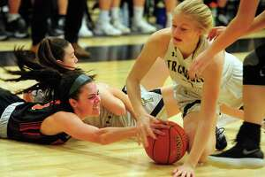 Ridgefield's Cara Sheafe (left) battles Trumbull's Emma Gentry for a loose ball during the FCIAC girls basketball semifinals Tuesday night in Trumbull.