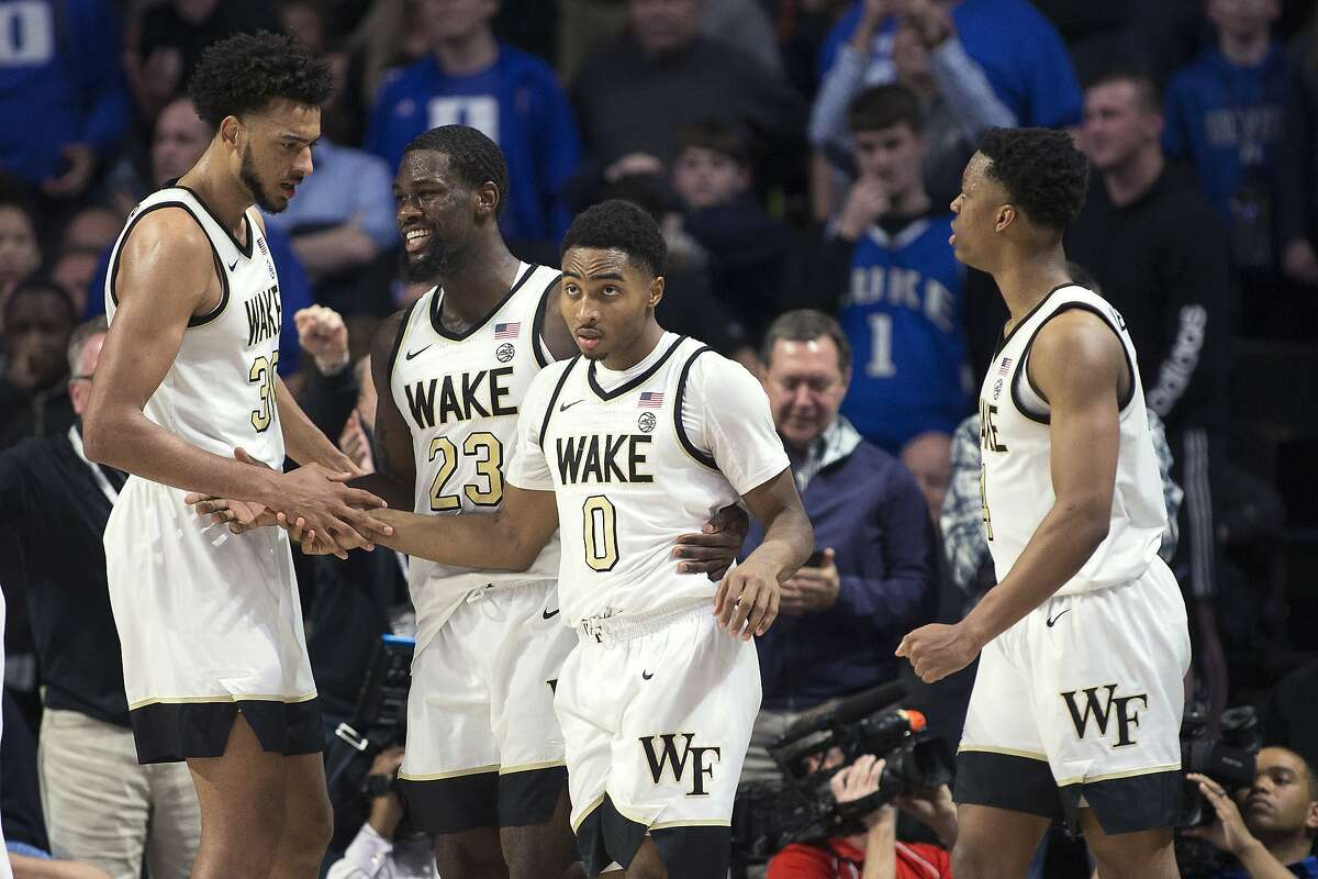 Wake Forest guard Brandon Childress (0) is congratulated by teammates Olivier Sarr (30), Chaundee Brown (23) and Jahcobi Neath (4) after scoring to send the NCAA college basketball game against Duke into overtime Tuesday, Feb. 25, 2020, in Winston-Salem, N.C. (AP Photo/Lynn Hey)