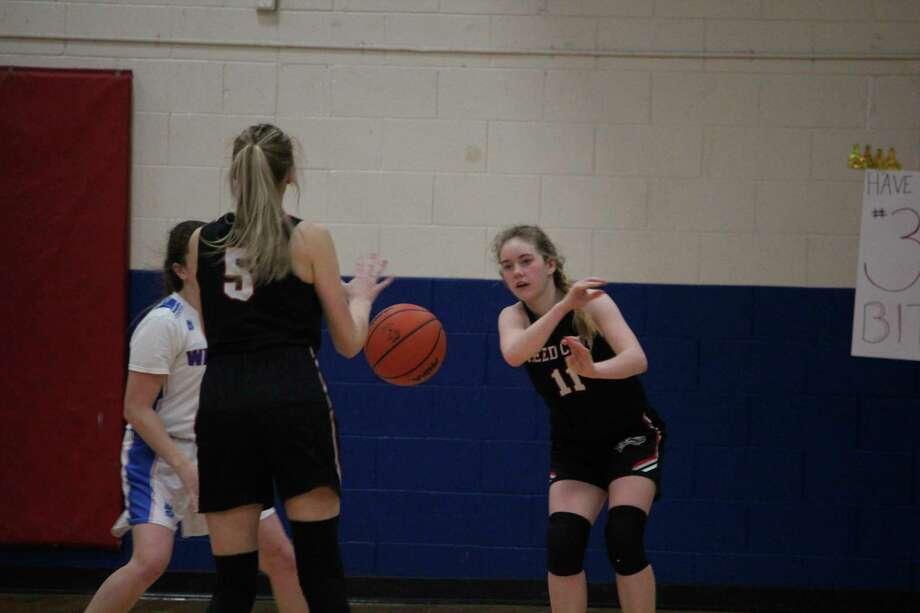 Reed City's Paige Lofquist (11) makes the pass to Christina Malackanich. (Herald Review photo/John Raffel)
