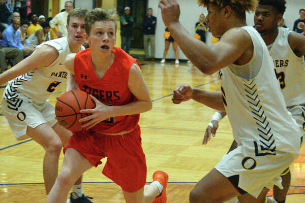 Edwardsville's Preston Weaver, left, drives to the basket during Tuesday's Southwestern Conference game at O'Fallon.