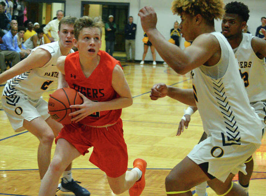 Edwardsville's Preston Weaver, left, drives to the basket during Tuesday's Southwestern Conference game at O'Fallon. Photo: Scott Marion/The Intelligencer
