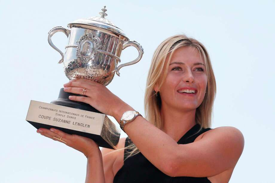 "(FILES) In this file photo taken on June 8, 2014, Russia's Maria Sharapova poses with the Suzanne Lenglen trophy in  a day after winning the Roland Garros French Tennis Open. - Five-time Grand Slam winner Maria Sharapova, one of the world's most recognisable sportswomen, on February 26, 2020, announced her retirement from tennis. ""Tennis  I'm saying goodbye,"" Sharapova said in an article for Vogue and Vanity Fair magazines. ""After 28 years and five Grand Slam titles, though, I'm ready to scale another mountain  to compete on a different type of terrain."" (Photo by Kenzo TRIBOUILLARD / AFP) Photo: KENZO TRIBOUILLARD, AFP Via Getty Images / AFP or licensors"