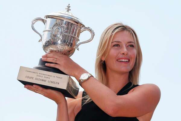 "(FILES) In this file photo taken on June 8, 2014, Russia's Maria Sharapova poses with the Suzanne Lenglen trophy in a day after winning the Roland Garros French Tennis Open. - Five-time Grand Slam winner Maria Sharapova, one of the world's most recognisable sportswomen, on February 26, 2020, announced her retirement from tennis. ""Tennis I'm saying goodbye,"" Sharapova said in an article for Vogue and Vanity Fair magazines. ""After 28 years and five Grand Slam titles, though, I'm ready to scale another mountain to compete on a different type of terrain."" (Photo by Kenzo TRIBOUILLARD / AFP)"