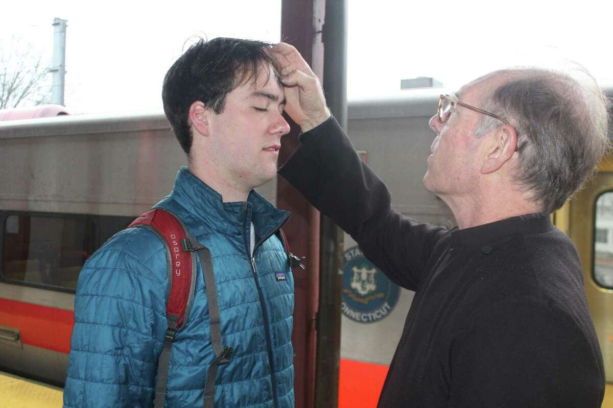 Gus Walsh receives ashes from his father, the Rev. Peter Walsh of St. Mark's Episcopal Church, who offered Ashes to Go to commuters at the downtown New Canaan Metro-North station the morning of Ash Wednesday, Feb. 26.