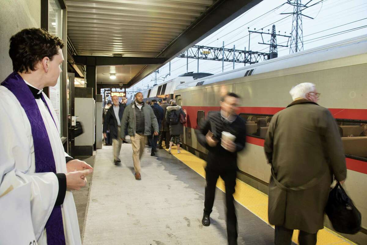 Derek Stefanovsky, assistant rector at St. Luke's Church, offers 'Ashes to Go' to commuters at Noroton Heights Train Station on Ash Wednesday. The church offers this program annually early mornings on Ash Wednesday.