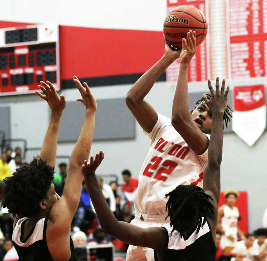 Alton's Jonathan Bolling (22) shoots over Carnahan defenders during an Alton Tourney game Nov. 27 at Alton High in Godfrey. The Redbirds were in Belleville on Tuesday and dropped a Southwestern Conference game to Belleville West. Photo: Greg Shashack / The Telegraph