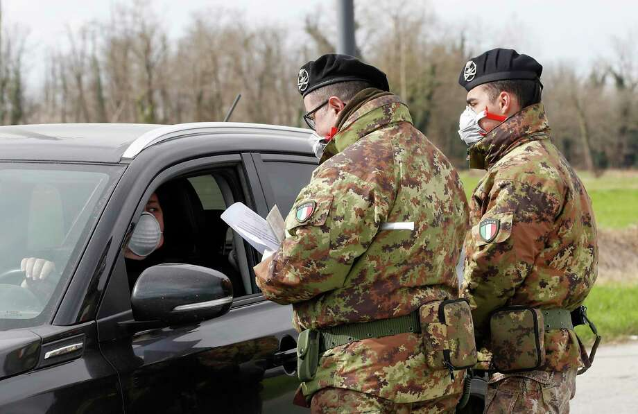 Italian Army soldiers check transit to and from the cordoned areas in Turano Lodigiano, Italy, Wednesday, Feb. 26, 2020. The viral outbreak that began in China and has infected more than 80,000 people globally, so far caused 374 cases and 12 deaths in Italy. (AP Photo/Antonio Calanni) Photo: Antonio Calanni / Associated Press / Copyright 2020 The Associated Press. All rights reserved