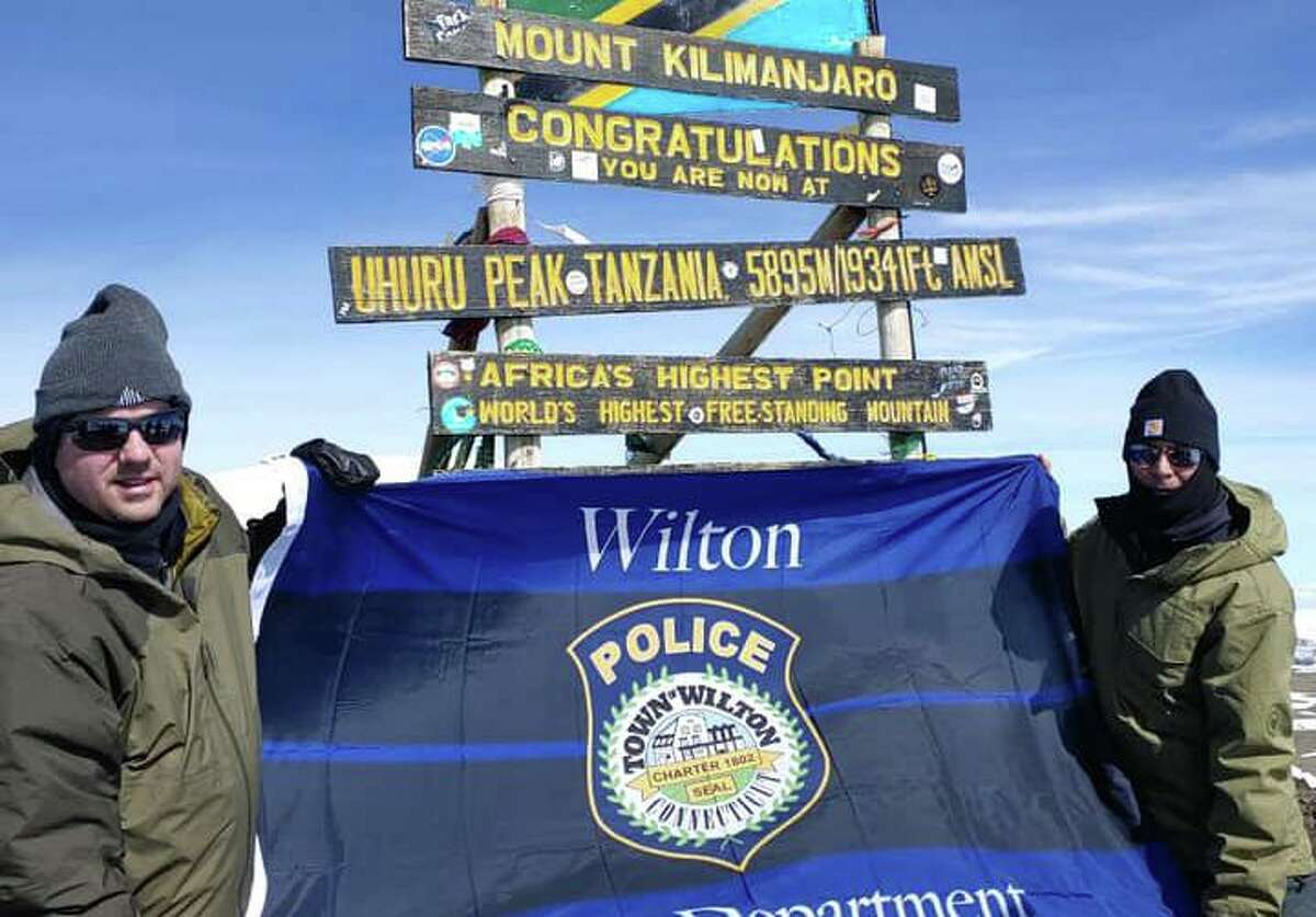 Lt. David hartman and Lt. Robert Kluk display a Wilton Police Department flag at the summit of Mount Kilimanjaro in Africa. They scaled the mountain as a fundraiser for Special Olympics.