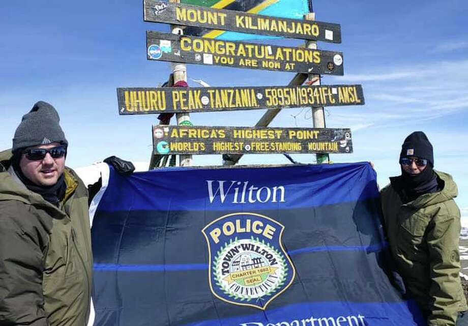 Lt. David hartman and Lt. Robert Kluk display a Wilton Police Department flag at the summit of Mount Kilimanjaro in Africa. They scaled the mountain as a fundraiser for Special Olympics. Photo: Contributed Photo / Wilton Police Department / Wilton Bulletin Contributed